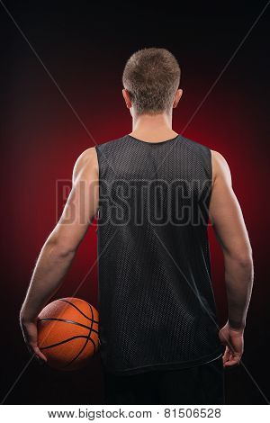 Caucasian basketball player holding the ball at his side