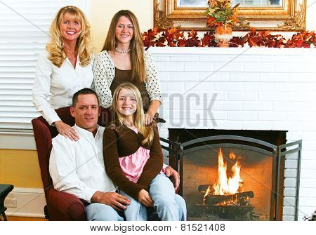 Portrait of a beautiful family by the fireplace, seasonally decorated with Autumn leaves.