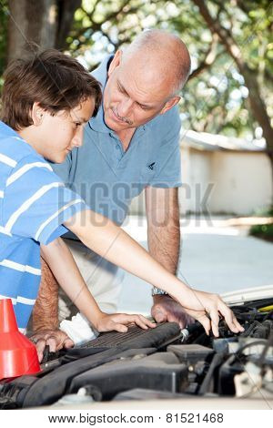 Father teaching his son how to do auto repairs, oil change, etc.