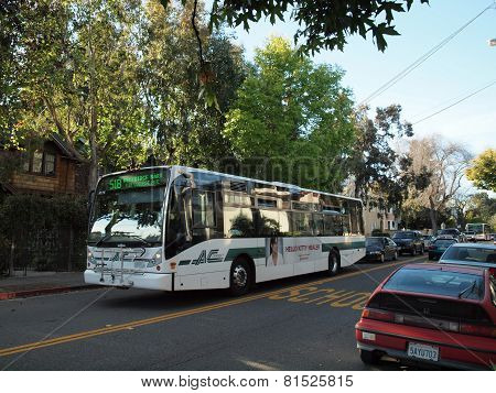 Ac Transit Bus With Ads Displayed On Side Driving Down The Street