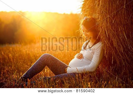 Young Pregnant Woman Sitting by the Haystack