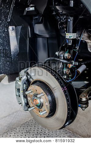 Front Disc Brake On Car In Process Of New Tire Replacement. The Rim Is Removed Showing The Front Rot