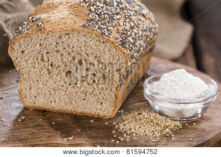 Fresh baked loaf of bread on rustic wooden background poster