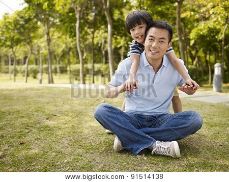 Asian Father And Son Having Fun In Park