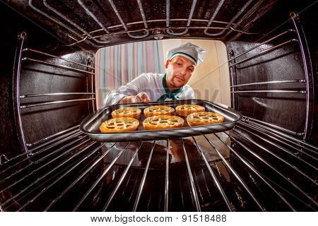 Chef prepares pastries in the oven, view from the inside of the oven. Cooking in the oven. poster