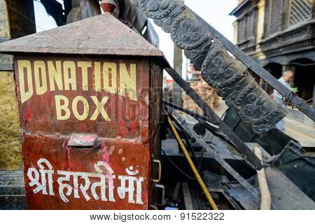 KATHMANDU, NEPAL - MAY 22, 2015: A donation box is standing among the rubble at Swayambhunath which was severely damaged after two major earthquakes hit Nepal on April 25 and May 12, 2015.