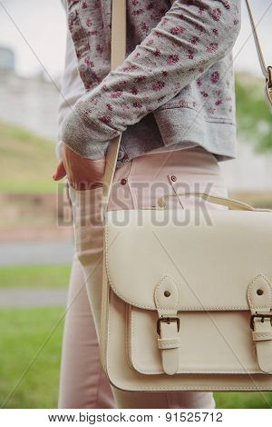 Young trendy woman holding white satchel bag outdoors