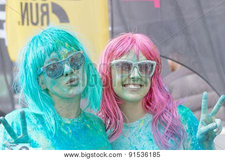Two Happy Girls Wearing Sun Glasses Covered With Color Powder