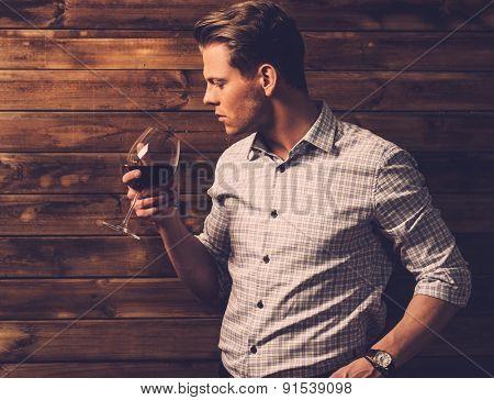Man tasting wine in rural cottage interior