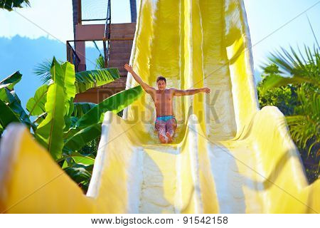 Excited Man Having Fun On Water Slide In Tropical Aqua Park