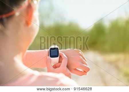 Smart watch for sport. Athlete wearing heart rate monitor. Runner looking at sports smartwatch going running outside. Female athlete tracking her activities using wearable technology. poster