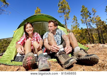 Camping people putting on hiking shoes by tent. Campers tying shoe laces getting ready for hike. Asian woman and Caucasian man living fun active lifestyle outdoors.