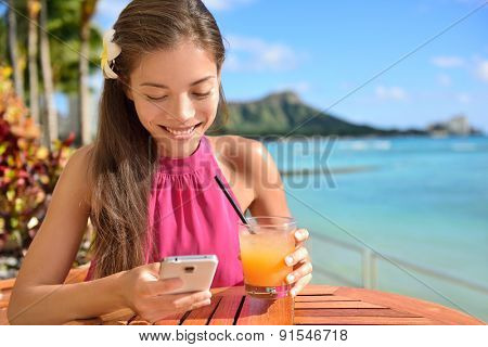 Woman using smartphone at beach bar drinking Mai tai Hawaiian cocktails having fun. Close up of woman holding alcoholic drink in Waikiki beach, Honolulu, Oahu, Hawaii, USA.