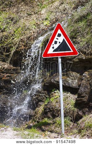 Small Waterfall Running Behind A Landslide Sign