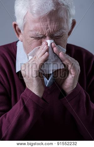 Old man with infection blowing his nose poster