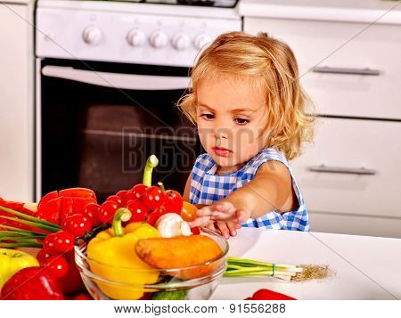 Child touching vagetable in colander at kitchen.