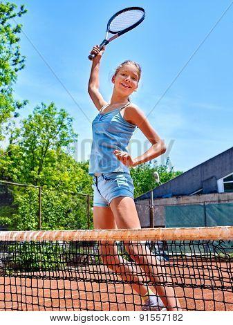 Girl teen sportsman with racket  jump near net on  tennis court.