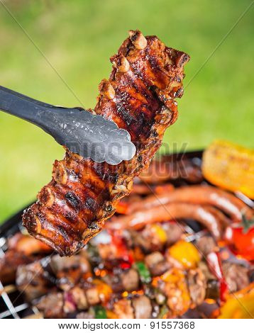 Delicious pork spareribs on grill grate, garden barbecue.
