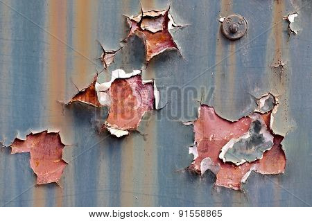 Texture of paintwork falling apart on metal surface