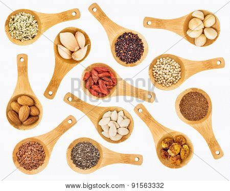 superfood grain, seed, berry, nuts and garlic abstract - top view of  random isolated on white wooden spoons