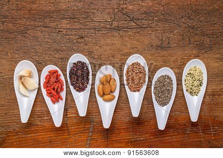superfood grain, seed, berry, nuts and garlic cloves abstract - top view of spoon bowls against rustic wood with a copy space