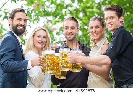 Co-workers after work meeting in beergarden drinking a glass of fresh beer, toasting to the viewer
