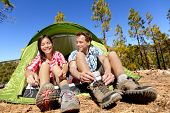 Camping people putting on hiking shoes by tent. Campers tying shoe laces getting ready for hike. Asian woman and Caucasian man living fun active lifestyle outdoors. poster