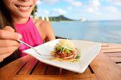 Tuna tartare. Raw ahi, Hawaiian food. Woman eating dish on Waikiki, Oahu, Hawaii. poster