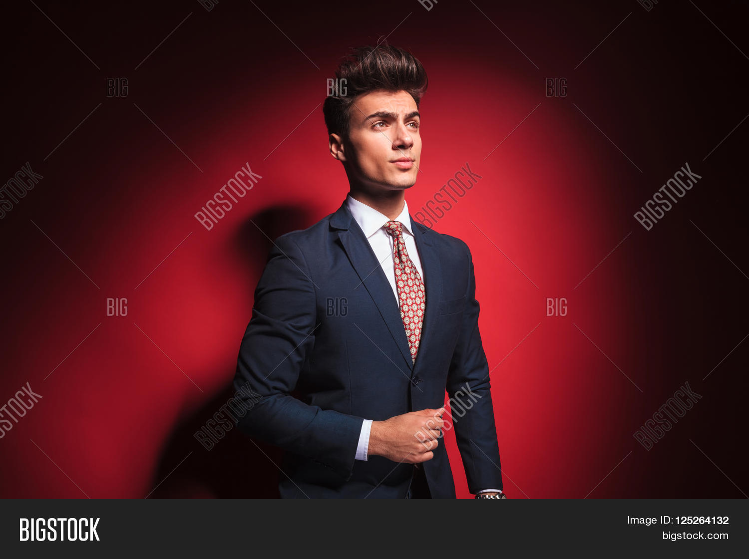 e2b3b39564e7 portrait of confident young businessman in black suit with red tie posing  arranging his jacket and