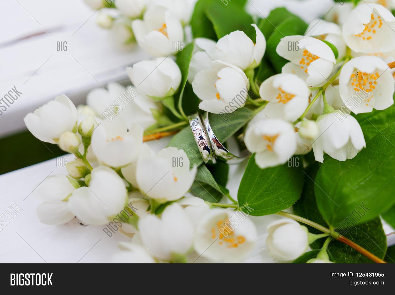 Golden wedding rings image photo free trial bigstock golden wedding rings with diamonds lie inside jasmine philadelphus flower in bridal bouquet izmirmasajfo