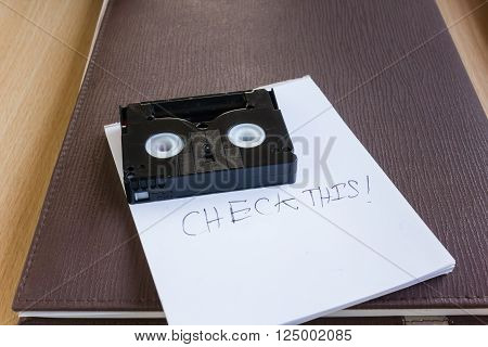 White CD or compact disk with note text word check this on dark blue document file on table with copy space