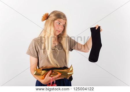 Bad gift concept - Beautiful girl not happy with her present she got: a pair of socks..