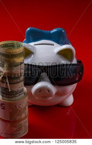 Piggy bank with black sunglass and rolls cash on red background