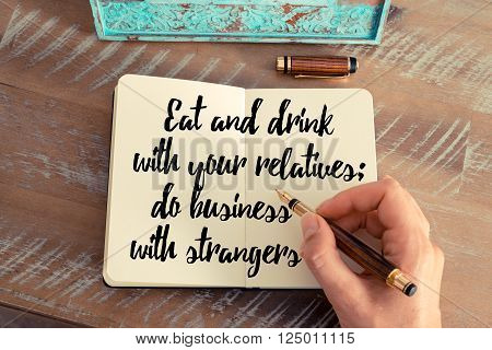 Retro effect and toned image of a woman hand writing on a notebook. Handwritten quote Eat and drink with your relatives; do business with strangers as inspirational concept image