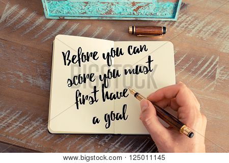 Retro effect and toned image of a woman hand writing on a notebook. Handwritten quote Before you can score you must first have a goal as inspirational concept image