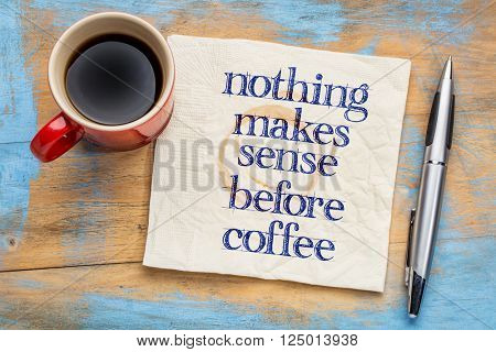 Nothing makes sense before coffee - handwriting on a napkin with cup of coffee against grunge wood background