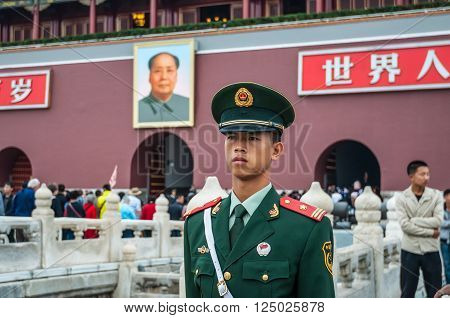 Beijing China - October 13 2013: A Chinese soldier stands guard in front of the Gate of Heavenly Peace between Tiananmen Square and The Forbidden City in Beijing China. Behind the soldier is a large portrait of Chairman Mao Zedong leader of the Communist