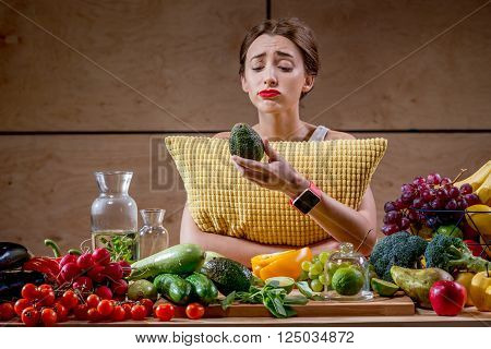 Sad woman with pillow watching reluctantly at the fuits and vegetables in the morning or in the evening before sleeping. Diet and healthy food concept