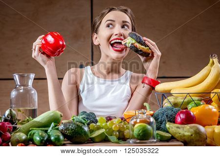 Young sport woman choosing between burger and healthy but tasteless food at the table full of fruits and vegetables in the wooden kitchen interior
