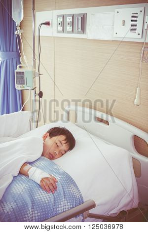Illness asian boy sleeping at modern and comfortable equipped hospital room with saline intravenous (IV) on hand. Health care and people concept. Vintage style.