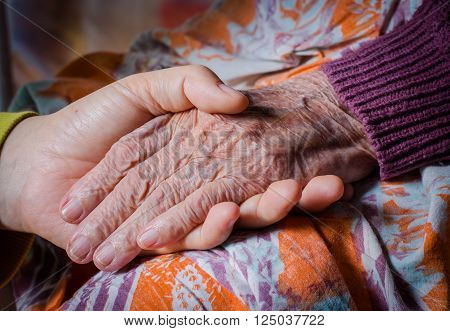 Young girl's hand touches and holds an old woman's wrinkled hand
