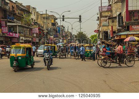 DELHI INDIA - 19TH MARCH 2016: A view along streets of Delhi during the day showing buildings Tuk Tuk Rickshaws motorbikes and people.