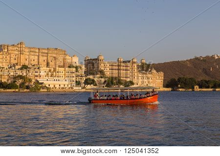 UDAIPUR INDIA - 20TH MARCH 2016: A view towards the City Palace from Pichola Lake in Udaipur during the day. Tour boats and people can be seen.