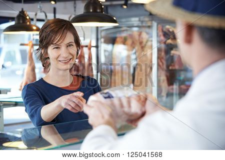 Female Customer Buying Meat In Butchers Shop