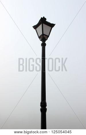 black street lamp post against a light sky