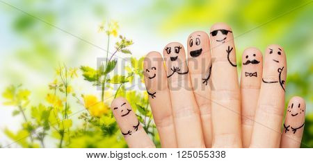 gesture, family, people and body parts concept - close up of two hands showing fingers with smiley faces over natural green herbal background