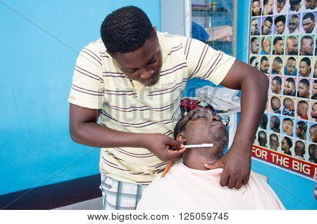 Cotonou, benin- june24; 2015: The barber shaves carefully beard of his customer.