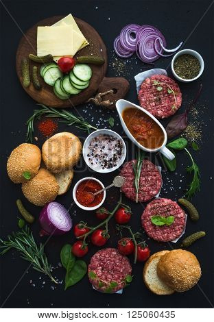 Ingredients for cooking burgers. Raw ground beef meat cutlets, buns, red onion, cherry tomatoes, greens, pickles, tomato sauce, cheese, herbs and spices over black background, top view
