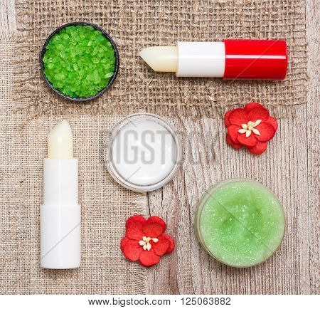Cosmetics for lip skin care: close-up of coarse sea salt, natural honey scrub with essential oils, moisturizing lip cream and balms with flowers on shabby wooden surface and sackcloth napkins