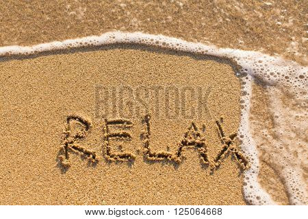 Relax - drawn on the sand of a sea beach.